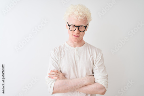 Fototapeta Young albino blond man wearing t-shirt and glasses standing over isolated white background skeptic and nervous, disapproving expression on face with crossed arms