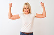 Middle age woman wearing casual t-shirt standing over isolated white background showing arms muscles smiling proud. Fitness concept.