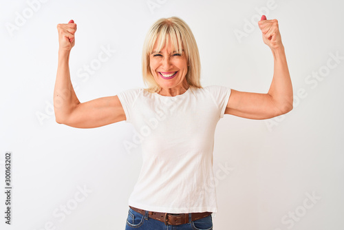 Valokuvatapetti Middle age woman wearing casual t-shirt standing over isolated white background showing arms muscles smiling proud