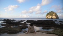 A Young, Brunette Woman With Long Hair, Dressed In A Loose Fit, Oversized T-shirt, Sits By Herself On The Shore With A Beautiful Background. Dipping Her Feet Into A Small Pool Of Water And Relaxing.