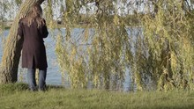 Woman Standing Beside Weeping Willow Tree At Water Side