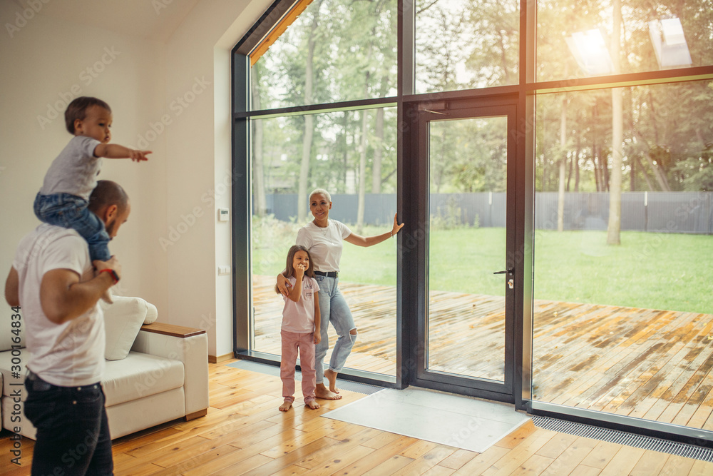 Fototapety, obrazy: Parents with children look at panoramic window together, relaxing together, spending time at home. Modern house interior