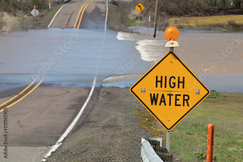 Fotografie, Tablou High water warning sign with floodwater crossing the road near Albany, Oregon