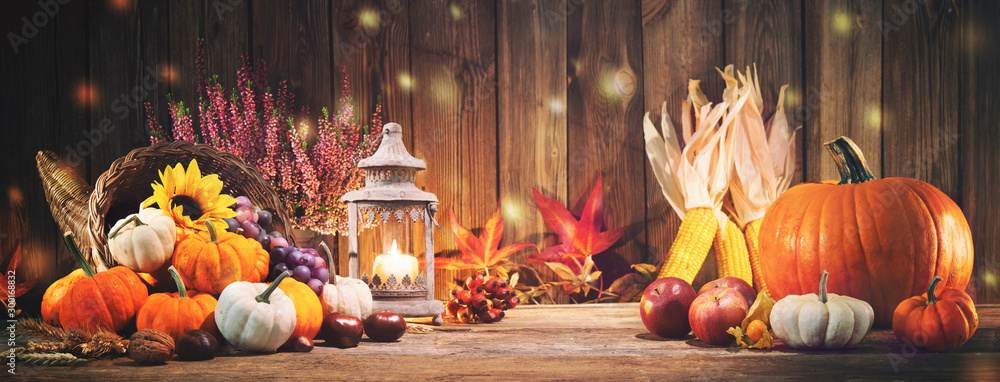 Fototapeta Pumpkins with fruits and falling leaves on rustic wooden table