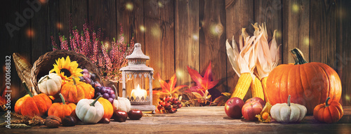 Wall Murals London Pumpkins with fruits and falling leaves on rustic wooden table