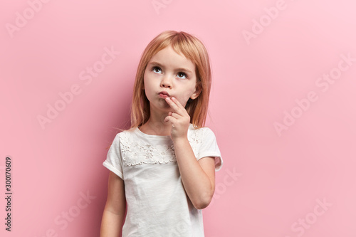 serious pensive girl with a finger on her chin looking up, close up photo. isolated pink background, idea, plan , faciala expression, reaction