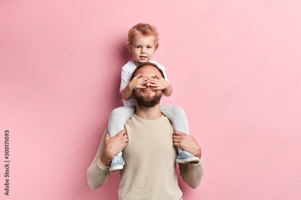 Fototapeta little boy closing his dad's eyes with palms, close up portrait, isolated pink background, studio shot