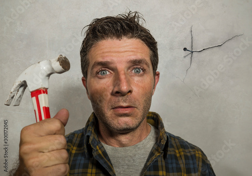 Cuadros en Lienzo funny portrait of man holding hammer after driving a nail for hanging a frame bu
