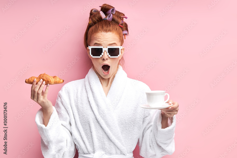 Fototapeta Young caucasian girl in white bathrobe stand with croissant and cup of tea. After shower in sunglasses.