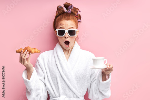 Fototapeta  Young caucasian girl in white bathrobe stand with croissant and cup of tea