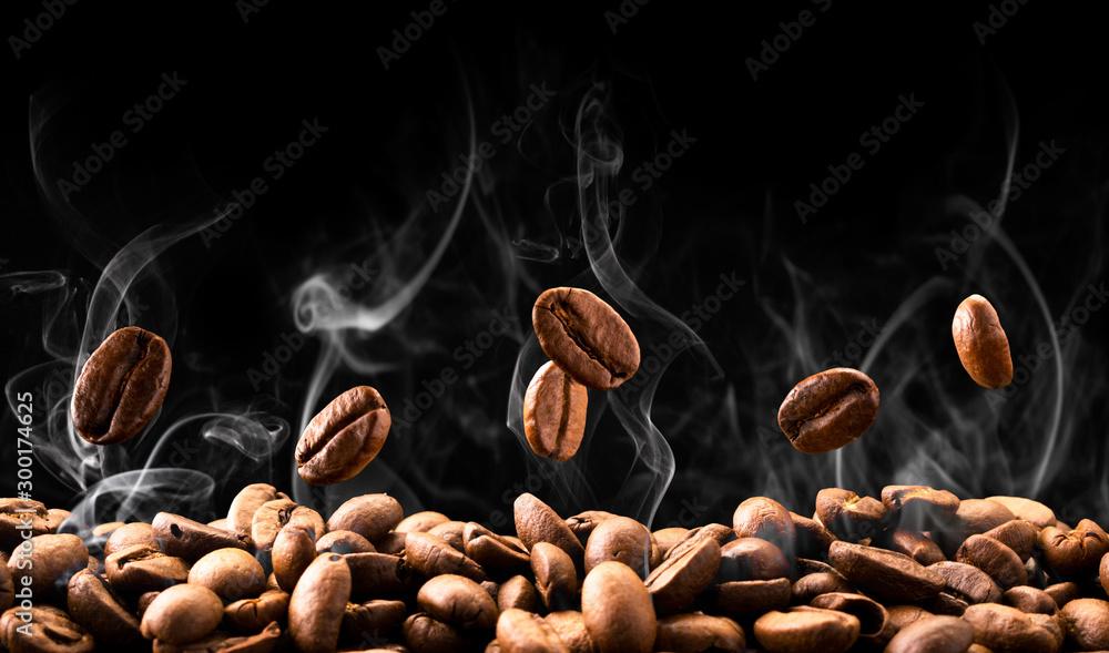 Fototapeta Coffee beans fall in smoke on a black background. Roasting coffee