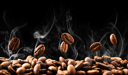 Panel Szklany Do kuchni Coffee beans fall in smoke on a black background. Roasting coffee