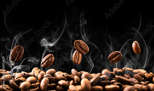 Papel de parede Coffee beans fall in smoke on a black background. Roasting coffee