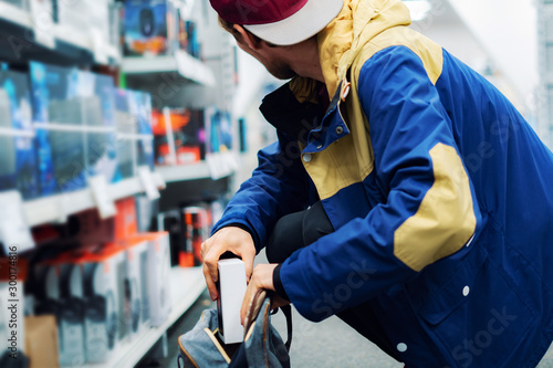 Fotomural close up consumer  thief's hands putting the new gadget in the pocket in the sto