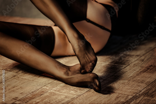 young woman legs and feet in stockings at wooden floor