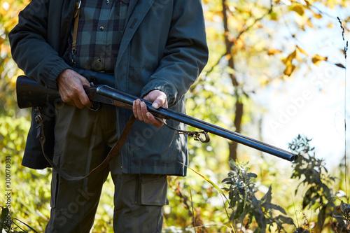 plakat Forest hunting on animals. Senior man holding shotgun, going to hunt