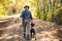 Ambush For Ducks With Dog In Autumn Forest. Hunter Man's Back With Dog Going To Hunt