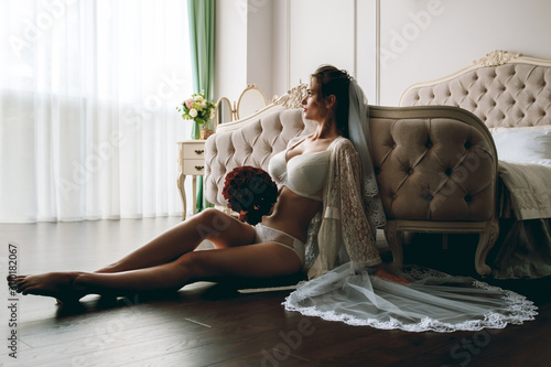 Morning of the bride. Portrait of a beautiful sexy girl in a white underwear. Young seductive woman in white linen and a peignoir. Beautiful bride with a bouquet of red roses.  Boudoir shooting. - 300182067