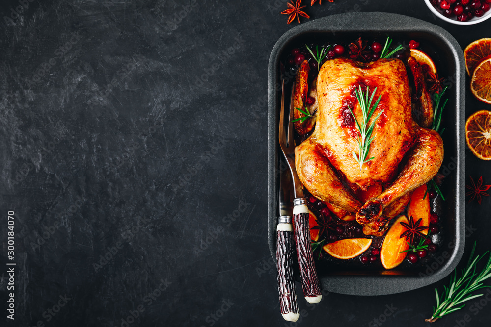Fototapeta Roasted chicken or turkey with spices, oranges and cranberries for Christmas or Thanksgiving