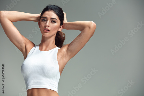 Portrait of an attractive, fit lady tying hair - 300185041
