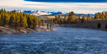 Madison River In Yellowstone Nation Park With Snow Top Mountains And Forest
