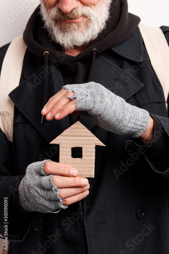 cropped old man wearing street clothes holding house made of cardboard, dream about shelter Fototapeta