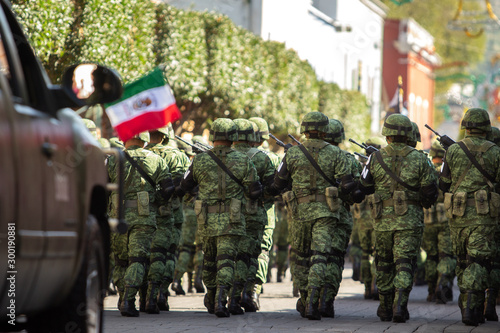 Fotografie, Obraz a group of mexican soldiers and a pick up truck during the annual parade to cele