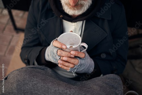 Homeless man's hands holding half empty mug with some coins at bottom Wallpaper Mural