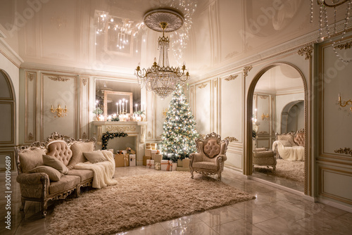 Obraz Christmas evening in the light of candles and garlands. Classic luxurious apartments with decorated christmas tree and presents. Living with fireplace, columns and stucco. - fototapety do salonu