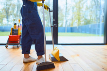 Side View On Young Cleaner Sweeping The Floor In Living Room, Panoramic Window Background. Cleaning Service