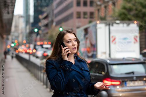 Valokuvatapetti Business woman talking on mobile walking down city street