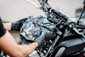 Worker repairing motorcycle headlight in the workshop