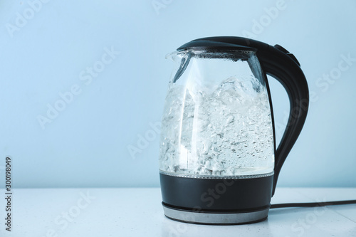 Fényképezés  Transparent electric kettle with boiling water on table