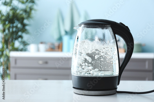 Fotografija Transparent electric kettle with boiling water on table in kitchen