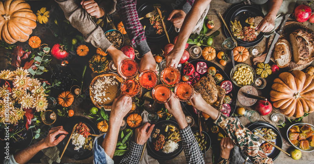 Fototapety, obrazy: Family celebrating Thanksgiving day. Flat-lay of feasting peoples hands clinking glasses with rose wine over Friendsgiving table with traditional Fall food, roasted turkey, pumpkin pie, top view