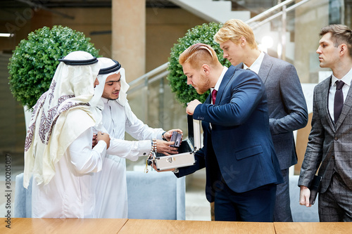 Fotografia, Obraz  Sheikhs in white suit look at new modern technology in case