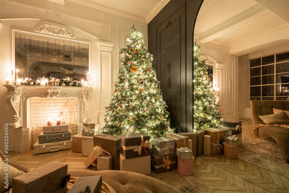 Fototapeta Christmas evening in the light of candles and garlands. Classic luxurious apartments with decorated christmas tree and presents. Living with fireplace, columns and stucco.