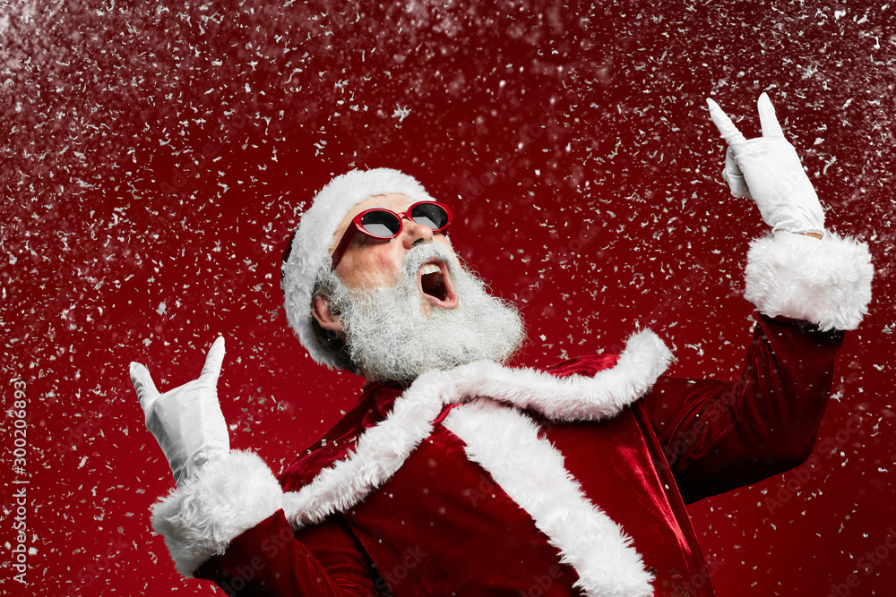 Fototapety, obrazy: Waist up portrait of cool rock Santa roaring over red background with snow falling, copy space