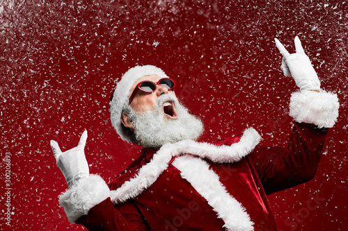 Waist up portrait of cool rock Santa roaring over red background with snow falli Canvas Print