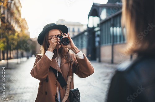 Fototapeta Outdoor smiling lifestyle portrait of pretty young woman having fun in sun city Europe autumn with camera travel photo of photographer Making pictures in glasses and hat with girlfriends obraz