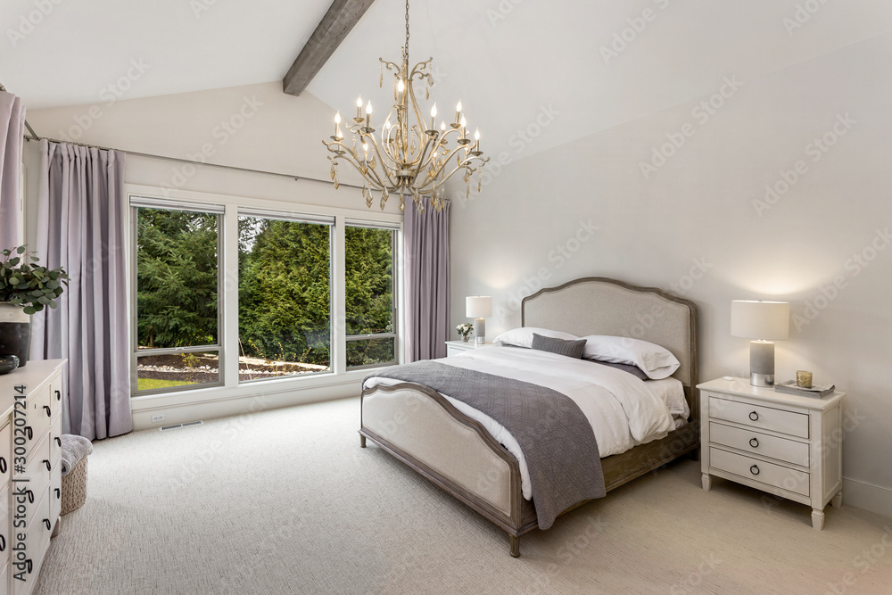 Fototapety, obrazy: Beautiful bedroom in new luxury home with wood beam and chandelier.
