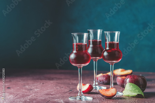 Fotografia Plums strong alcoholic drink in grappas wineglass with dew