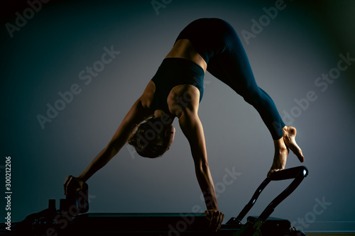 Fotografie, Tablou  Young girl doing pilates exercises with a reformer bed