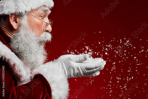 Fototapeta Side view portrait of classic Santa Claus blowing snow while standing against red background, copy space obraz