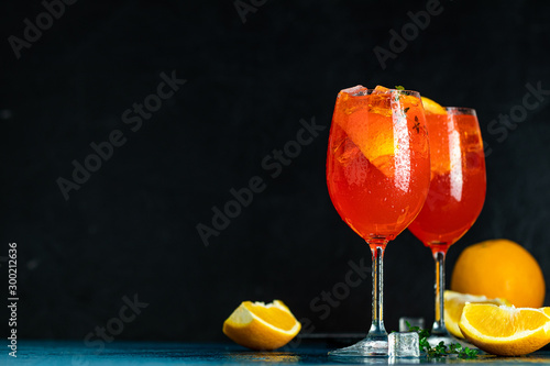 Fond de hotte en verre imprimé Bar Two Aperol spritz cocktail in big wine glass with oranges, summer Italian fresh alcohol cold drink. Dark bar counter background with tools, summer mood concept, selective focus