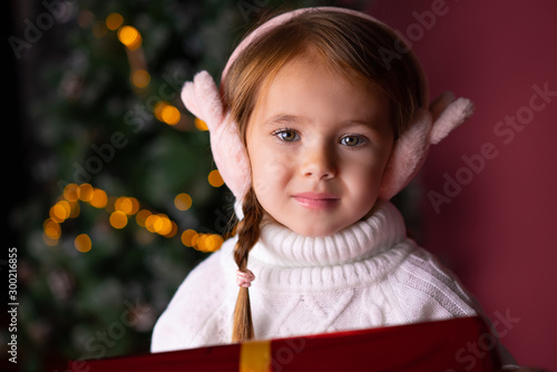Beautiful little girl in the hat sitting near presents and christmas tree Canvas Print