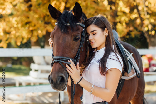 Fotografie, Obraz Smart animal. Happy woman with her horse on the ranch at daytime.
