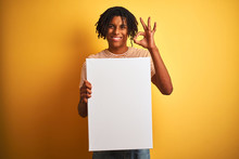 Afro American Man With Dreadlocks Holding Banner Over Isolated Yellow Background Doing Ok Sign With Fingers, Excellent Symbol