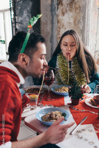 Cheerful friends at the table eating pasta, spaghetti hanging out their mouths Canvas Print