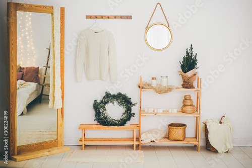 Obraz Scandinavian hallway interior with big mirror and shoe storage bench near white wall. Hallway with christmas decor. - fototapety do salonu